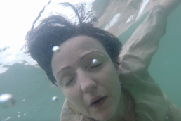A person's face in close-up, underwater with eyes closed. The water is cold and blue, and water bubbles pass the camera.