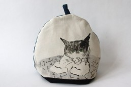 A fabric teacosy, onto which is painted a black and white cat with green eyes. She bends her paws towards herself.