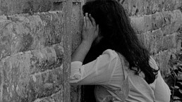 A person with long dark hair peers through a hole in an old wooden door of a stone building