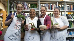 Four women of different ages in aprons holding clay objects including a glazed spoon, a flower-holder and a bowl. They are standing in a library.