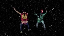 Two figures in colourful clothing leap into a dark sky filled with stars