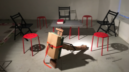 An image of around 8 chairs painted black and red, sited in a gallery space around an strange cardboard construction