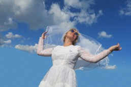 An image of a white-veiled woman in a bridal dress, wearing sunglasses and looking to the horizon against a blue sky