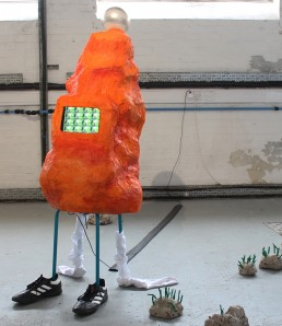 Bright orange paper mache blob like sculpture with stick legs wearing football boots