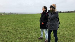 two girls in winter coats and wolley hats standing in a field with sheep in th edistance