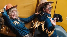 Two women with blonde hair, wearing demin and dressed like cowgirls with gold fringes on their clothing, striking a pose by a yellow DHL lorry