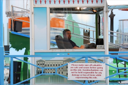 seated man starring from his ticket cabin for a big wheel