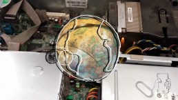 A mixed media image including the mucky insides of an electronic device, a globe and a line drawing of a hand clutching a phone