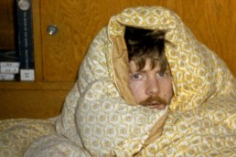man wraped in a mustard coloured duvet with a moustache