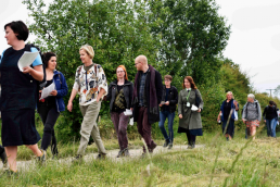 A group of people walk through the countryside, talking in pairs
