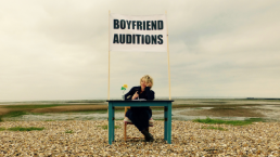 A blonde woman sits behind a desk, which is located on a shingle beach. Above her head is a large sign, reading: Boyfriend Auditions