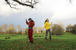 two ladies dancing in a field, one wearing red and the other wearing a yellow sweatshirt
