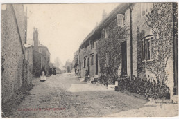 black and white old image of Burton in East Coker, a lone figure standing in the road